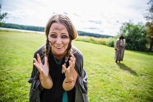 """""""Hjälp mig"""". Lina Tiilikainen spelar en pestsmittad kvinna under medeltiden. Hon följs av en läkare i särskild pestmask och heltäckande kläder."""