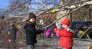 Julia och Klara i full färd med att fästa färggranna fjädrar på årets påskbjörk.