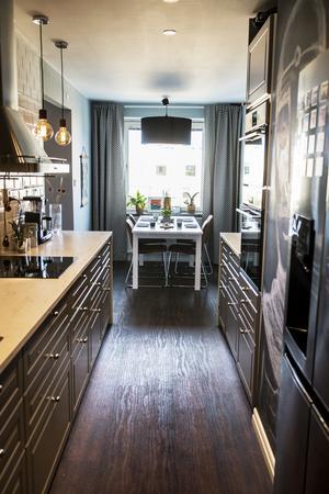 Köket går i grått, både skåpluckorna och väggarna har fått parets favoritfärg. Den långa bänkskivan är en marmorimitation.