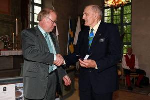 Lars Israelsson ger Per Erik Andersson, Gällö, pris för sina förträffliga insatser inom Heimbygda.  Foto: Håkan Degselius