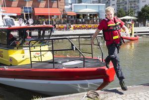 Robin Skog hoppar i land från båten Rescue Hans Carlsson.