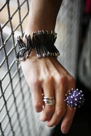 Kostymören Cilla Rörby från Gävle har gjort Lisbeth Salanders kläder i filmerna.Armband av säkerhetsnålar med svarta pärlor på, kan man göra själv eller köpa för 50 kronor på Deåsånt. Den taggiga ringen kostar 80 kronor.