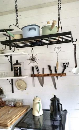 Köksdelen i huset. På de stora planken hänger knivar och kastruller dinglar från taket.