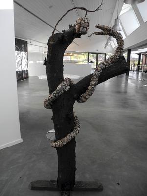 Ett träd med en slingrande stenorm av Anneli Jämte möter besökarna.