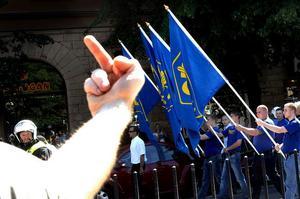 STOCKHOLM 2007-06-06En motdemonstrant pekar finger åt representanter för nationalsocialistisk front med fanor i högerextrema Folkets Marsch på nationaldagen. Foto: Ingvar Karmhed/SvD/SCANPIX