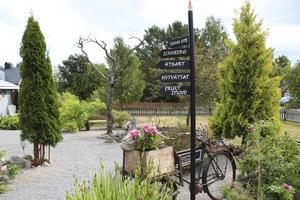 Trädgården är uppdelad i små rum, en skylt i början visar vägen.