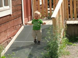 Henry Brus (14 månader) tycker det är roligt att gå nedför den lutande rullstolsrampen vid skolan på friluftsmuséet vid Vallby.