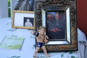 Elly visar upp  ett fotografi av Alexander tillsammans med pastor-Wiggo. Även en leksaksfigur av