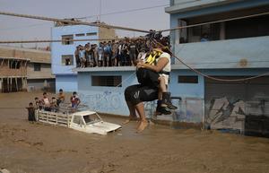 En kvinna och hennes dotter firas översvämmade gatan i huvudstaden Lima med hjälp av en lina.