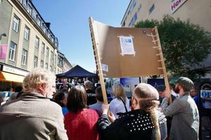 """När Sverigedemokraternas kandidat skulle få presentera sig, lyfte några i publiken upp ett plakat med texten """"inga rasister på våra gator""""."""