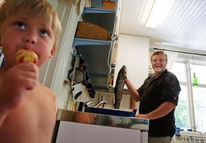 Dagens fångst ska snart tillredas av Bernt medan barnbarnet Leon tittar på.