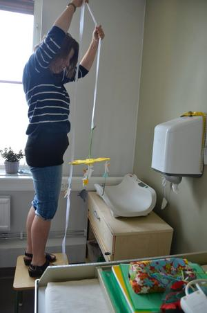 Annika Sjögren inreder sitt rum med färgglada saker för de kommande barnbesöken.
