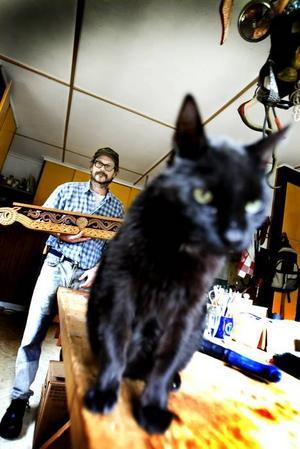 ENSAM MED SJU KATTER. Träsnidaren Magnus Aldenby bor för sig själv i byn Ulvkisbo några kilometer från Österfärnebo. Den svarte hannen Lille Fan och sex andra katter håller honom sällskap. Foto: Britt Mattson