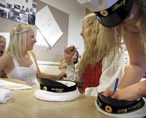 Lovisa Åkesson och Klara Sahlén fick sina studentmössor signerade innan betygsutdelningen.