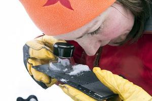 Karin studerar vilken typ av kristaller som olika snölager består av.