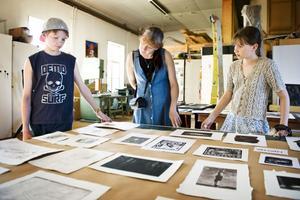 Karl, Alise och Jevgenija Stepins tittar på grafiska blad hos Dag Wallin.
