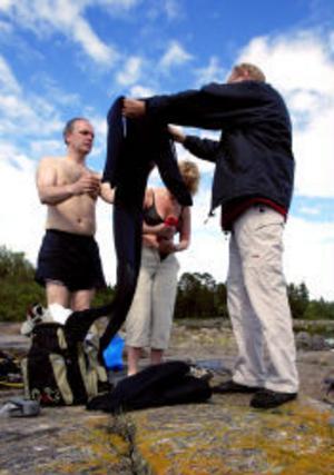 Kent Olsson hälper Lotta Bovidson och Anders Lindroos att prova ut våtdräkter.