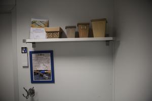 På en hylla i rummet finns information om kremering. Separat eller gemensam kremering. Vilken urna man vill ha.
