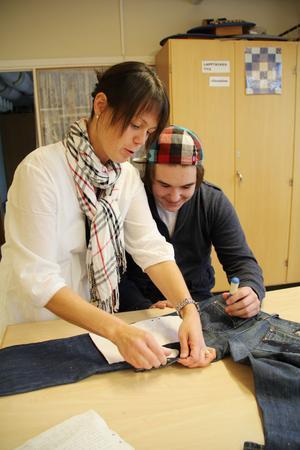 Jennie Forsblom hjälper Kevin Lindblom med att placera ut mönsterdelarna på hans pappas gamla jeans. Nu ska de förvandlas till grytvantar.