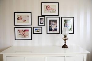 Familjebilder pryder en vägg i sovrummet.