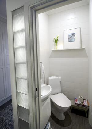 Kul lösning med glasbetong vid toaletten i entrén. Innanför ska det bli en svag belysning som ger ett mjukt ljus ut till hallen. Toalettstolen är placerad diagonalt för att få plats med alla rör som behövde byggas in i väggen.