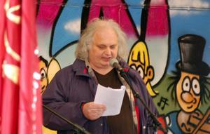 Göran Greider. här sumboliskt avporträtterad mellan en av arbetarrörelsens röda fanor och en av populärkulturens graffitigubbar.