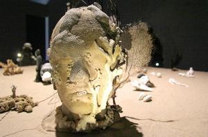 Ett bord är täckt av olika typer av föremål och gestalter. En av dem är ett självporträtt, där Tilda Lovell har täckt sigtt huvud med snäckskal och koraller.