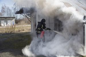 Tredje larmet. En bil brinner i en carport.