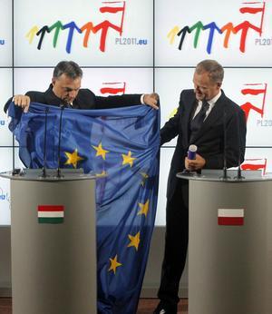 Ungerns premiärminister Victor Orban lämnar över EU-flaggan till Polens premiärminister Donald Tusk, för att symbolisera att Polen nu tagit över efter Ungern som EU:s ordförandeland.