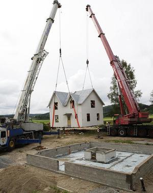 Huset med storleken nio gånger nio meter lyfts enkelt upp. Många bybor samlas för att se hur det ska gå.