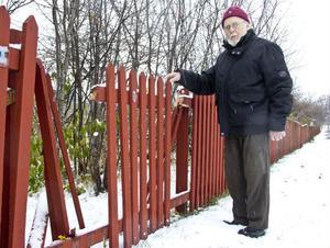 Ture Leijner intill det sönderhuggna staketet.