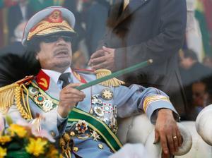 Här sitter ledaren Moammar Gadhafi bakom skottsäkert glas vid en militärparad i Tripoli år 2009.