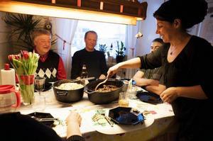 Irada Lundgren serverar en festmåltid till vännen Östen Wiik och maken Erik Lundgren för att fira Mona och Leylas uppehållstillstånd.