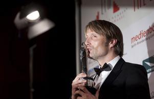 Mads Mikkelsen firar sitt pris på European Film Awards.