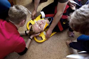 Känsligt läge. Att fixera ett huvud på en ryggfixeringsbräda är inte det lättaste. En enda liten rörelse i nacken kan förstöra för patienten. Kenneth Bergström från Gävle räddningssällskap håller huvudet fixerat på låtsaspatienten Sara Johansson.