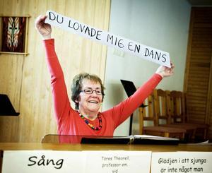 Kristina Jönsson, körledare för PRO-kören i Ramsele, håller upp en av de 120 textremsorna som kören ska hitta melodin till. Att sång ska vara glädje tar man fasta på i Ramsele. Öppet hus hos PRO-kören är en av många aktiviteter nu när hälsoveckan drar i gång.
