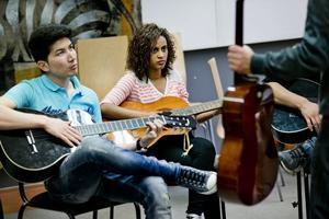"""Världens orkester. På måndagskvällarna träffas deltagare i """"Världens mentor"""" på Kulturskolan. Mohsen Nazari och Hana Alemayehu tränar gitarrackord."""
