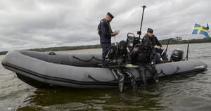 Dykern som sitter längst till vänster på båtens reling håller en metalldetektor i handen som används för att lokalisera ammunition som ligger begravd i bottensedimenten.