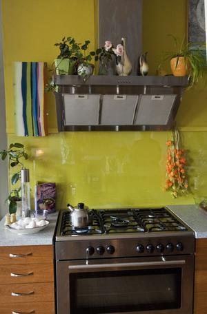 Det äpplegröna är Colette Luotsinens egen blandning, hon gillar färg. Det brandgula på väggen är japansk lykta som hänger på tork, en psysalis-växt.  Den mångfärgade lampan är faktiskt Ikea.