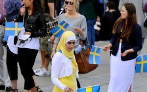 Flaggor. Svenska flaggor är väl synliga bland åskådarna.