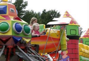 Linn Källman hjälper en glad lillasyster Oline med karusellflyget.