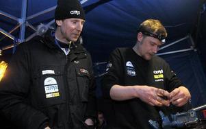 Mekanikern Anders Bergman skruvar med en av de trasiga drivknutarna. Hasse Gustafsson kan bara titta på. Foto: Lars Ingvar Eriksson