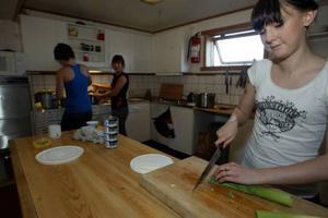 Josefin Larsson hackar purjolöken och Anna Andersson och Evelina Lindström håller grytan kokande. Foto: Håkan Degselius