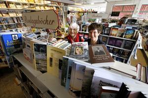 """Vid """"gubbhyllan"""". Siri Linusson drev bokhandeln i 30 år innan dottern Åsa Lidberg tog över för 16 år sedan. Här vid hyllan med Roslagslitteratur flockas de manliga kunderna."""