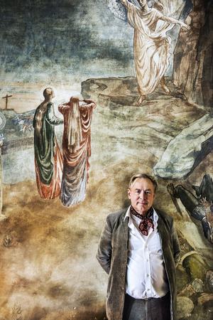 Ragnhild Nordensten har målat väggmålningarna som dominerar Magnus vardagsrum. Bakom honom syns Jesu uppståndelse.