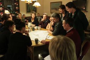 Alla studerar ritningen över den nya Skarpåkerskolan som visas upp av rektor Stefan Karlstedt.