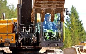 Arne Gustavsson, Skedvi, grävmaskinist vid vägbygget. Han får ett usb-minne av Diana Wohlberg, som han sätter in i grävmaskinen. Foto: Johnny Fredborg