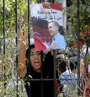 Förebild. En demonstrant i Kairo håller upp ett porträtt av Turkiets premiärminister Tayyip Erdogan. Arkivbild: Khalil Hamra/Scanpix
