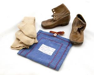 """Oemotståndligt. Barnskor och strumpor från 1920-talet. På lappen står det """"Yngves skor och strumpor (1 år)""""."""