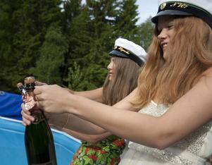 Sofi Holmlund och Johanna Högerås sprättar champagneflaskorna.